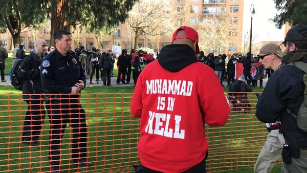A pro-Trump demonstrator in an anti-Muslim sweater observes antifa gathering in Vancover, Wash. (Mike Bivins)