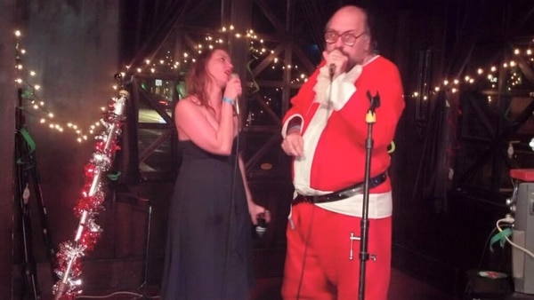 """Christine Heeley doing karaoke with John """"Elvis"""" Schroder at a BarFly Christmas party. IMAGE: Courtesy of Christine Heeley."""