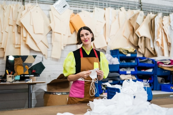 """FABRIC OF OUR LIVES: Portland Garment Factory owner Britt Howard is producing 6,000 """"frontline barrier masks"""" per week at her Montavilla textile factory. (Christine Dong)"""