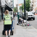 A Clean and Safe employee passes two downtown Portland campers. (Laurel Kadas)