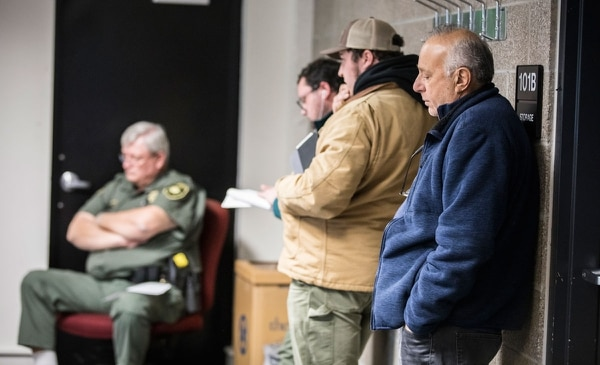 Hector Hassen (in blue) outbid the two auction regulars (to his right) for a North Portland home on March 13. The lender opened the bidding at $207,578.84. Hassen paid $258,000.(Sam Gehrke)