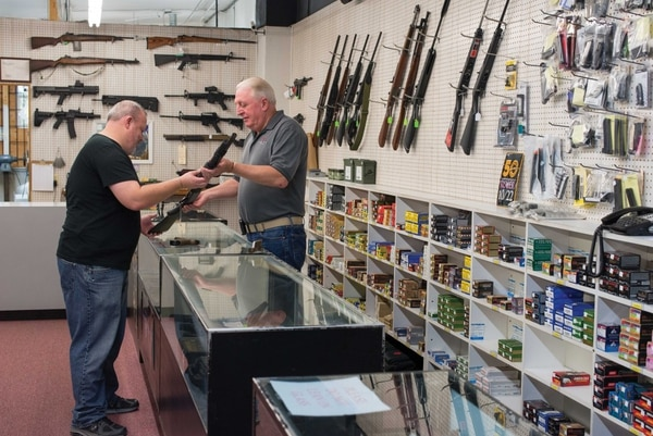 SURE SHOT: John Semm (right) has sold firearms to Portlanders for the past three decades. (Photo by Ryan LaBriere)