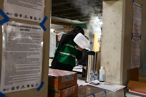 A Multnomah County worker at the NE Irving St Garage winter shelter fills up a water boiler used to make hot ciders & coffee. (Justin Yau)