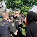 Mayor Ted Wheeler talks to police while taunted by protesters on April 29, 2017. (Joe Michael Riedl)