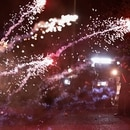 A firework explodes on the driveway of the Penumbra Kelly Building in front of Portland police officers. (Justin Yau)