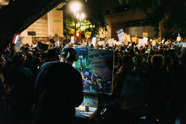 On one street corner, an artist sets up an easel each night and works on an oil painting of the crowd trying to tear down the courthouse fence. (Alex Wittwer)