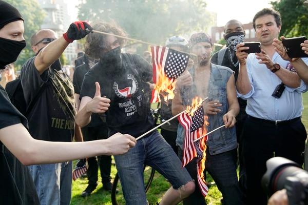 Antifascists burn flags in Tom McCall Waterfront Park (William Gagan)