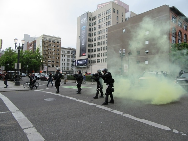 Riot police take aim with crowd control weapons at Black Bloc down the street after declaring a riot downtown (Corey Pein).