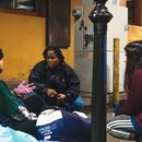 HOME STRETCH: Perlia Bell (center) works for JOIN, a nonprofit that helps people on the streets of Portland find services. On a winter evening last year, she handed out blankets and socks to people sleeping beneath the Burnside Bridge. (justin katigbak)