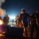A line of riot police tears down a flaming barricade to pursue protesters on Stark Street. (Alex Wittwer)