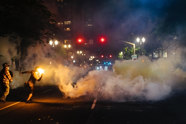 A protester hurls a flare toward police lines. (Alex Wittwer)