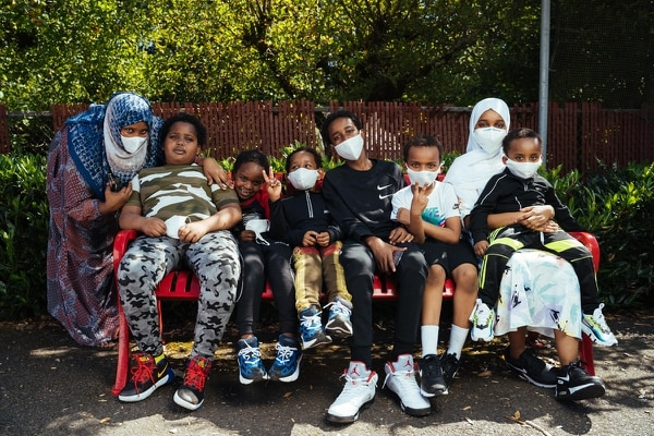 FAMILY PORTRAIT: Amran Goni (left) and seven of her eight children pause from playing at the Lincoln City Park playground. She raises the children as a single mother. (Alex Wittwer)