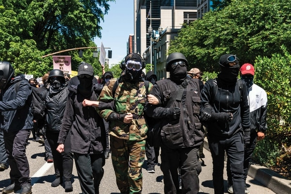 Antifascists gear up in masks, helmets and goggles to protect themselves from pepper spray and blows from both right-wing brawlers and the police. (Justin Katigbak)