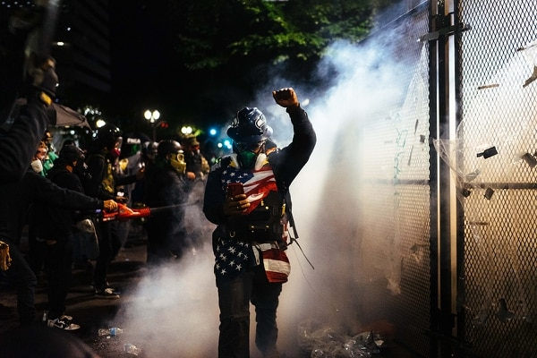 """Its a beautiful struggle"" says Tavis Greenwood, draped in an American flag, as he walks past a wall of tear gas while recording on the front lines. (Alex Wittwer)"