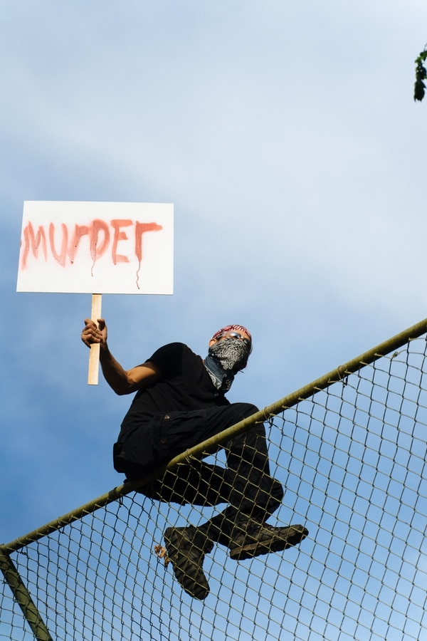 A protester sits atop the batting cage at Peninsula Park. (Alex Wittwer)