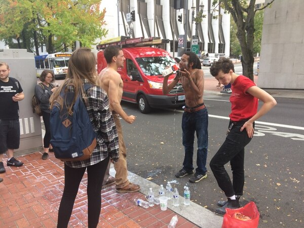 Donald Thompson III and other protesters wash pepper spray out of their eyes near Portland City Hall on Oct. 12, 2016. (Julia Comnes)