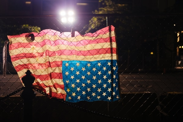A U.S. flag was tied upside down to the fence on the southside of the Multnomah County Justice Center, with numerous doughnuts adorning the fencing. (Alex Wittwer)