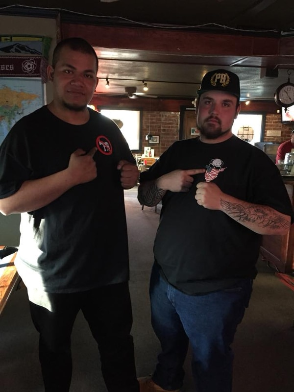 "Tustiala ""Tiny"" Toese and Donovon Flippo pose together in a photo showing off their right-wing t-shirts. (Multnomah County District Attorney's Office)"