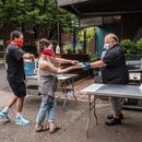 Michael Waters, partner/chef of Carina Lounge on Northwest 21st Avenue, serves a burger to a customer. (Brian Burk)