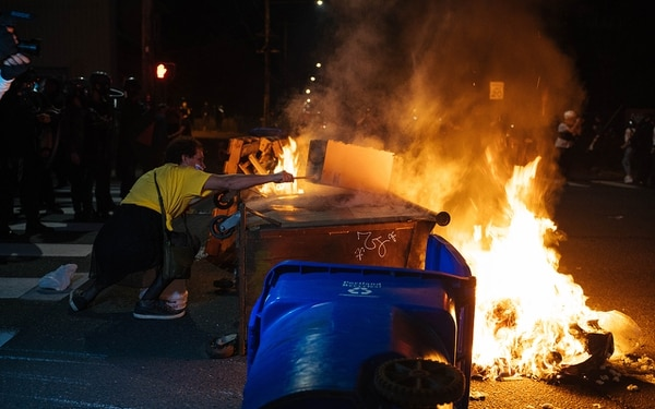 Protrsters erect a flaming barricade at the intersection of Southeast 117th Avenue and Stark Street. (Alex Wittwer)