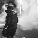 Portland police officer, amid tear gas. (Dylan VanWeelden)