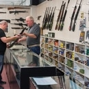 John Semm lets a customer examine a rifle at Shooter's Service Center in St. Johns. (Ryan LaBriere)
