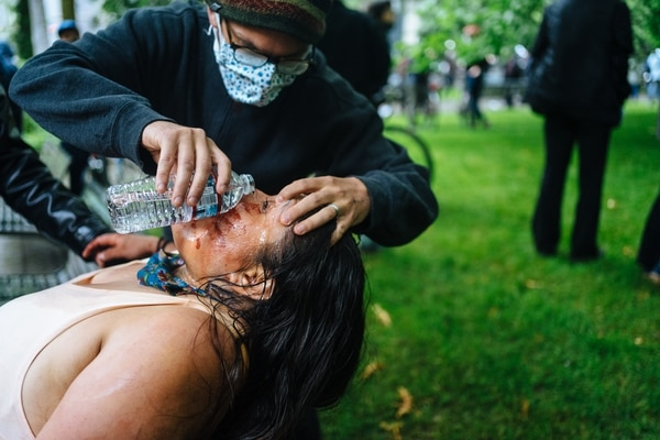 A protester pours water in the eyes of a Native American protester, who was incapacitated by tear gas after the police declared the protest an unlawful assembly. (Alex Wittwer)