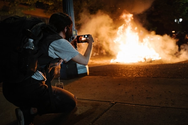 Alissa Azar records a mattress fire outside of North Precinct. (Alex Wittwer)