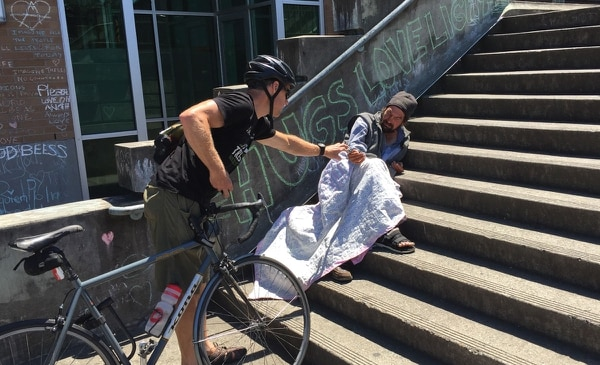 STEP BY STEP: A passerby gives spare change to a man sleeping at the Hollywood Transit Center. (Thacher Schmid)