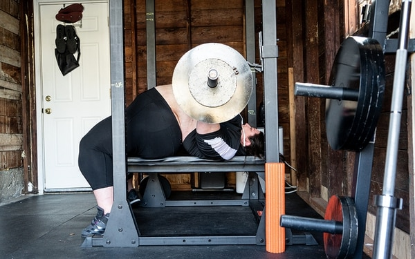 OFF THE BENCH: Malone benchpresses 150 pounds during her warmup before her training session begins. While working out at home, Christina surpassed a 200-pound benchpress lift, something she'd struggled to do at an in-person gym. (Christine Dong)
