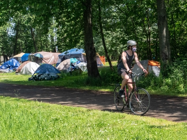 The Peninsula Crossing Trail mostly gives the campers some space from the surrounding neighborhood; their closest neighbors are an apartment building. (Brian Burk)