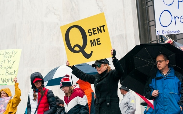 """DRAMA IN REAL LIFE: A woman attending the May 2 Reopen Oregon rally holds a sign that says """"Q Sent Me."""" (Aaron Wessling)"""