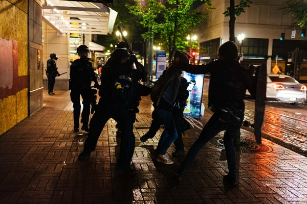 A police officer uses a baton to strike a protester who had raised a skateboard. (Alex Wittwer)