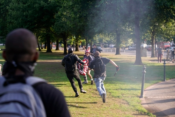 Antifascist protesters chase a counter-protester who stole a flag they were burning on June 30. (William Gagan)