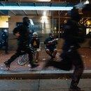 Police rush past two bystanders waiting for the bus on Southwest 6th Avenue. (Alex Wittwer)