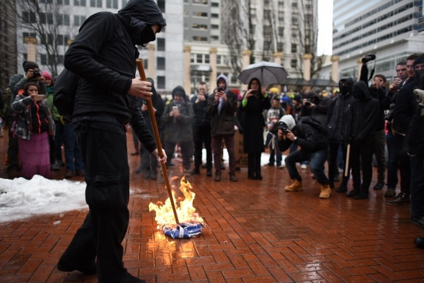 Protesters burn American flag in Pioneer Courthouse Square on Jan. 20, 2017. (Joe Riedl)