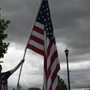 A man with an oversized American flag listens to speakers in Salem on May 1, 2021. (Justin Yau)