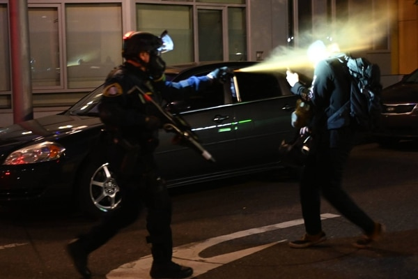 A Homeland Security agent deploys mace on a Portland protester filming on his cellphone during an
