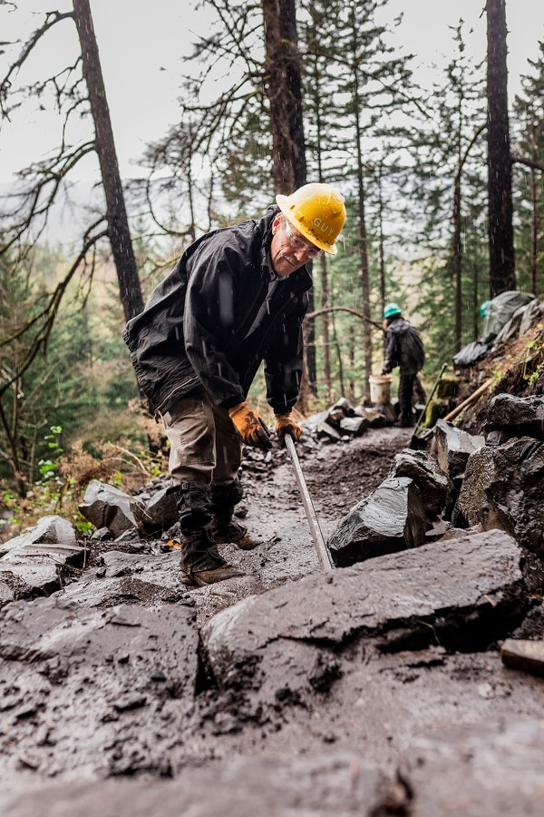 Guy Hamblen, 72, levers a basalt stone into place on the Horsetail Falls trail, where he leads a trail party for Trailkeepers of Oregon. The stone will form the bottom step of a staircase that will be the result of about 300 volunteer hours by the time of its completion. (Wesley Lapointe)