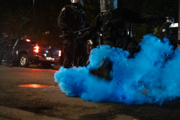 A police officer attempts to kick a smoke firework away from the street and towards protesters, but misses. (Alex Wittwer)
