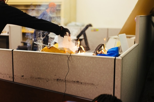 A man fuels a fire on the desk inside the Justice Department. (Alex Wittwer)