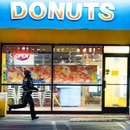 A riot cop sprints past the west entrance of Heavenly Donuts in July. (Dylan VanWeelden)