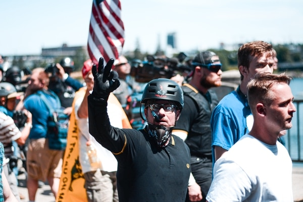 "A right-wing protester gives the ""OK"" sign to onlookers. (Liz Allan)"