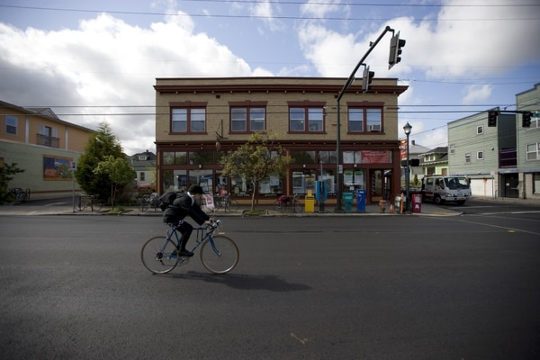 A cyclist passes in front of the Alberta Co-op Grocery in NE Portland. (Darryl James)