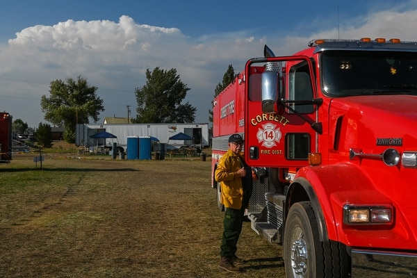 GEARING UP: A Corbett volunteer firefighter dons his protective shirt as he boards his water tender vehicle in Bly, Ore. (Justin Yau)