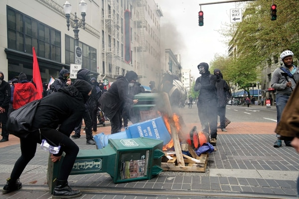 In May 2017, demonstrators in black block lit fires and toppled newsstands near Pioneer Place mall. (William Gagan)