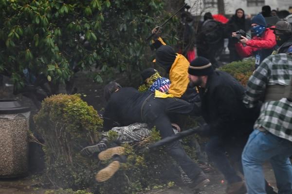 Multiple Proud Boys tackle a leftist protester into a bush outside the Oregon Capitol. (Justin Yau)