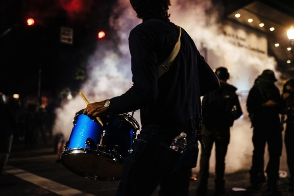 A drummer beats out a rhythm as tear gas pours out from the federal courthouse. (Alex Wittwer)