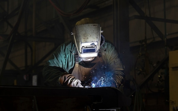 A welder works on side assemblies for intermodal rail cars at the Gunderson Rail Car Plant in Portland, Oregon on Tuesday, Jan. 15, 2013. (Natalie Behring/Bloomberg News)