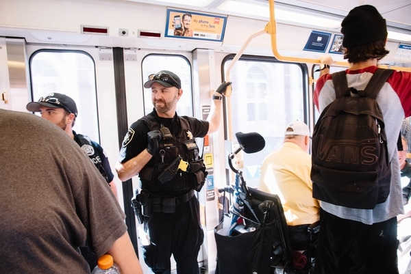 A transit police officer rides a MAX train. (Joe Michael Riedl)
